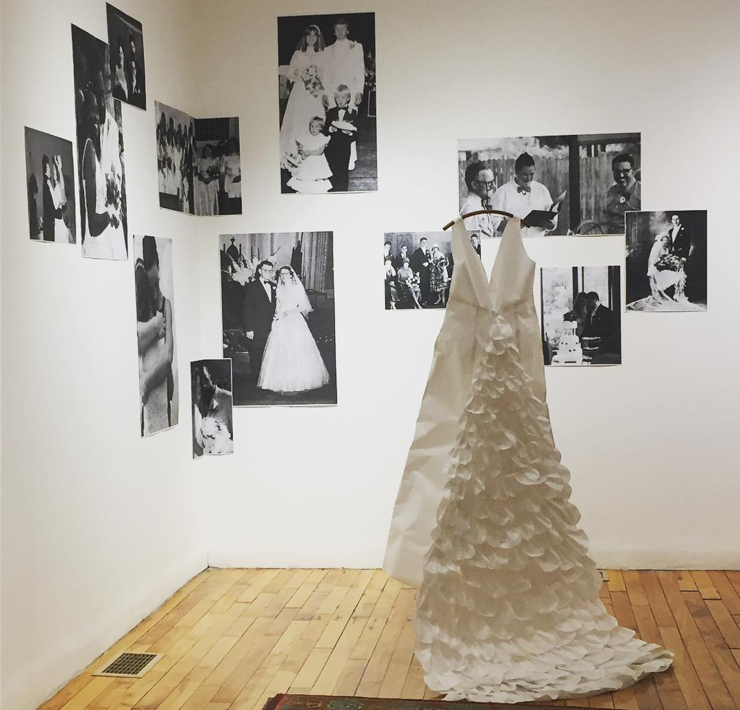 paper wedding dress in front of large black and white wedding photos