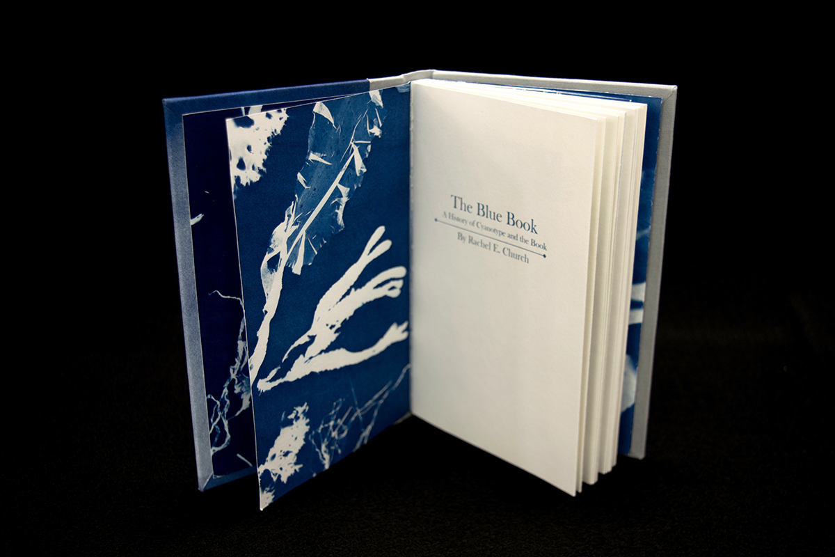"title page of ""The Blue Book"" showing cyanotype end pages printed with seaweed."