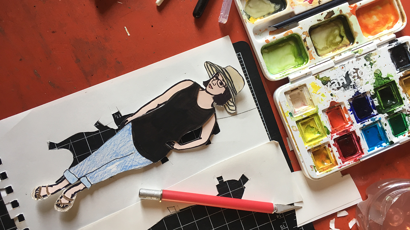 paper doll of the artist on worktable with paint set, exacto knife, and cutting mat.