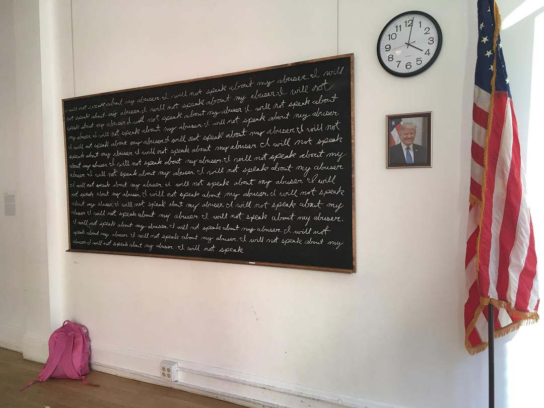 "photo of installation which includes from right to left and small pink backpack on the floor, large chalkboard with ""I will not speak about my abuser"" written over and over agian, school clock and photo of President Trump on wall, and large standing American flag."