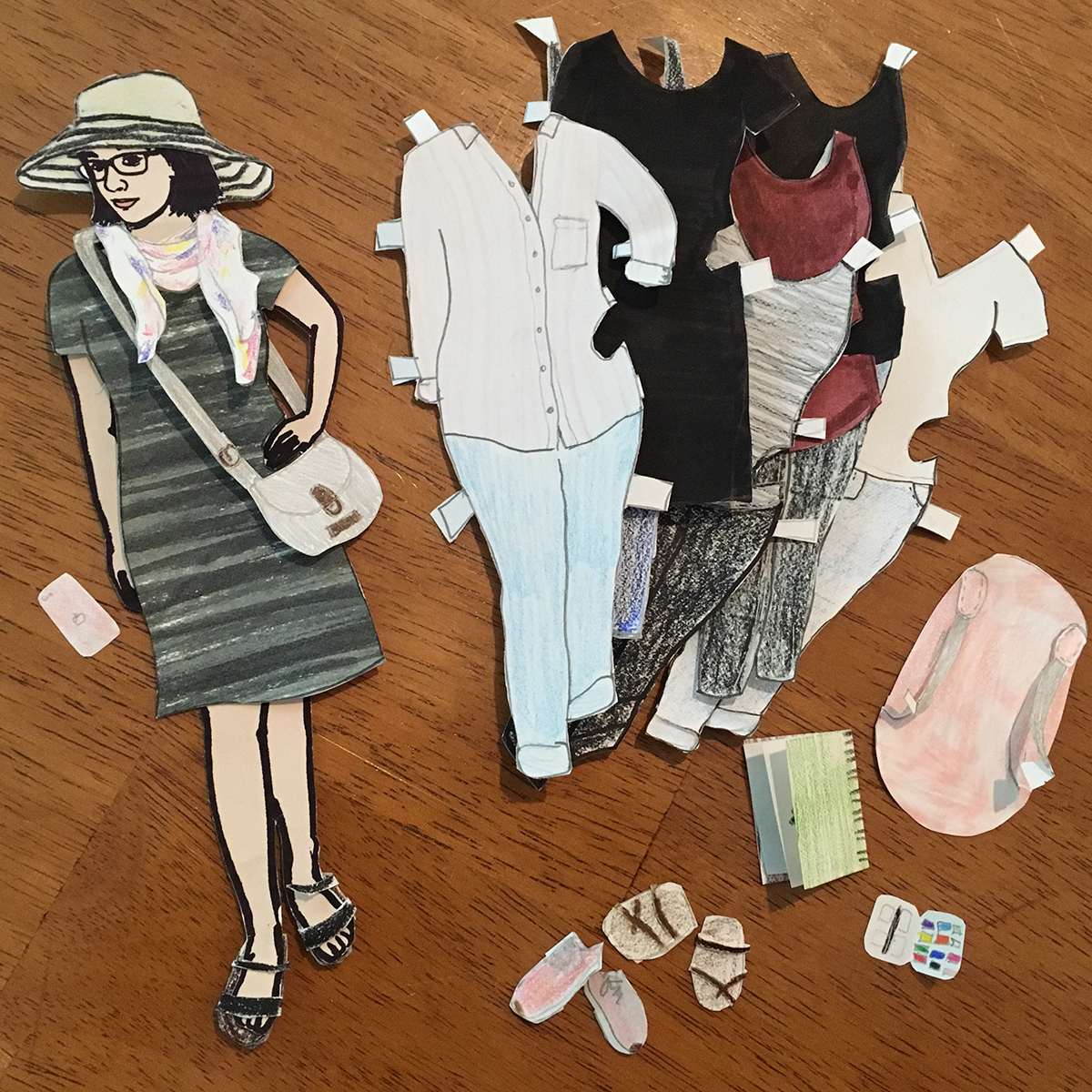 paper doll of the artist with full set of paper clothing and accessories, including 8 outfits, 3 sets of shoes, purse, scarf, sunhat, iphone, backpack, sketchbook, and paint set.
