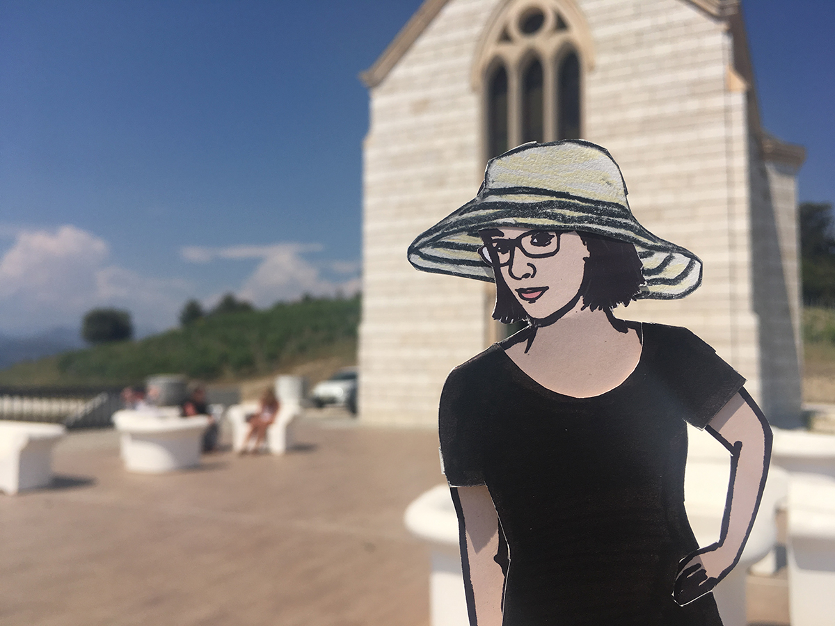 paper doll of the artist in front of chapel at a french winery