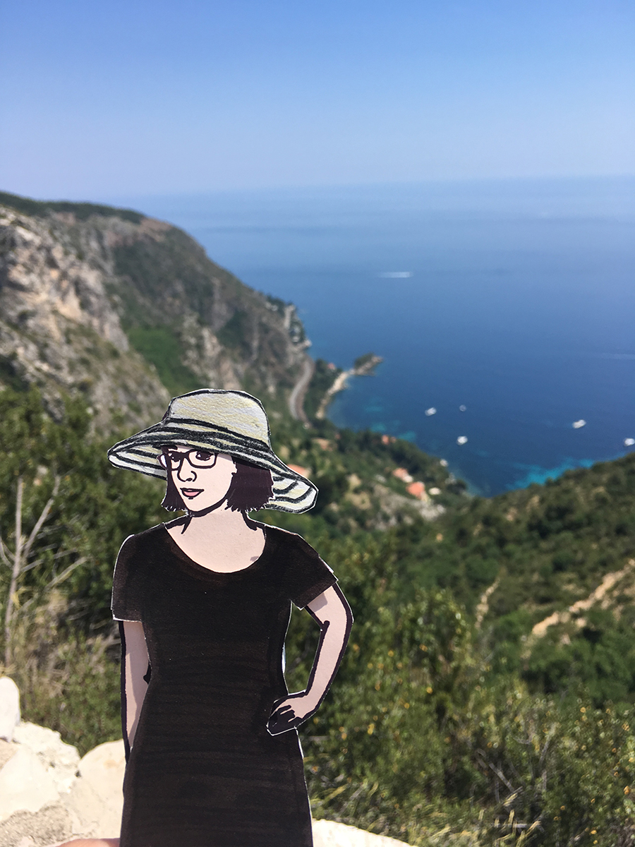 paper doll of the artist in front of French Rivera coastline