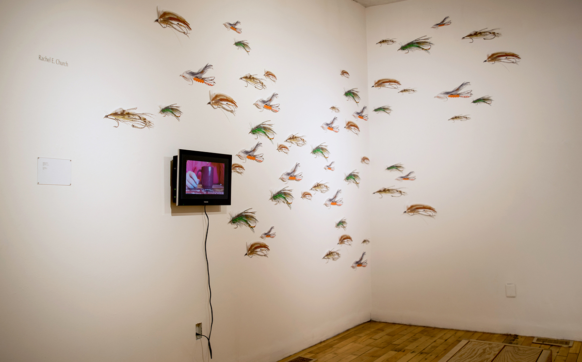 "installation with wall mounted tv monitor and 55 17"" long digital illustrations of fishing lures, cut out and mounted on the wall"