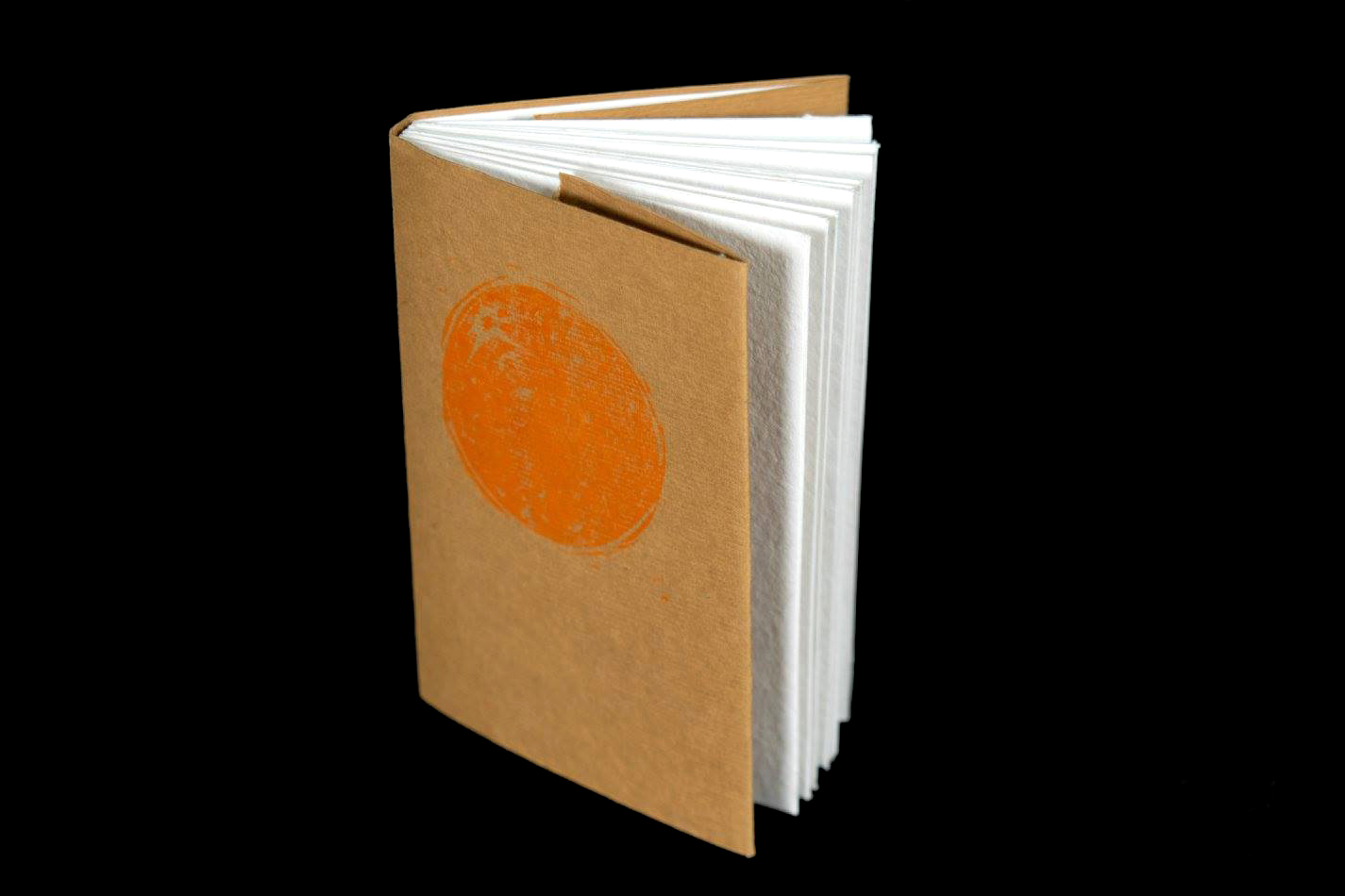 small artist book with brown cover featuring image of an orange