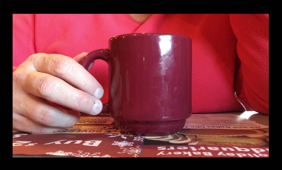 """still from """"Passed Down"""" video of hand holding coffee mug at a diner table"""