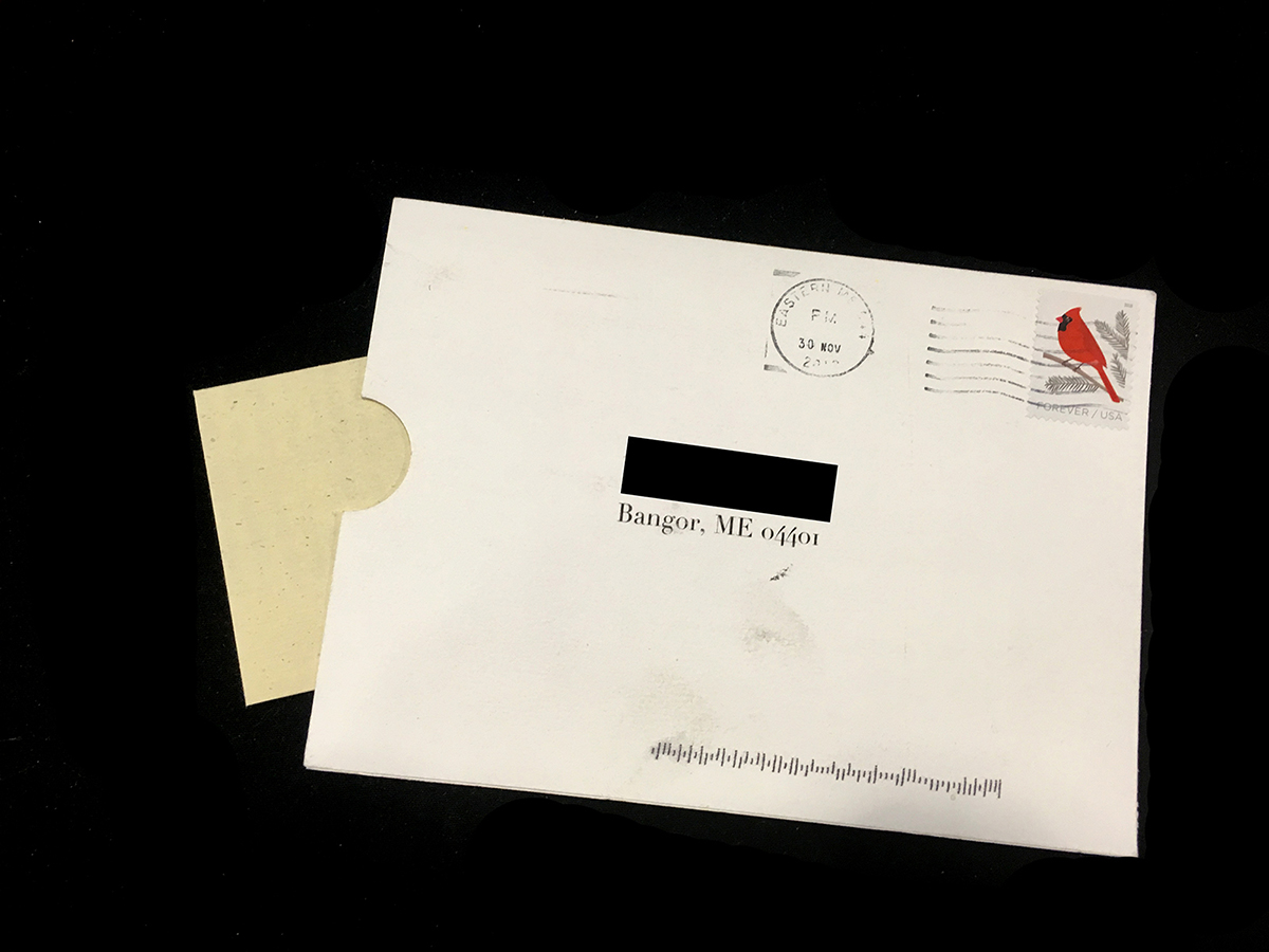 mailed postcard with opening on left side that has a small, folded piece of paper sticking out