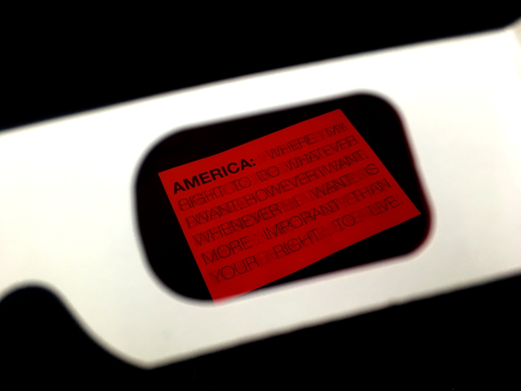 Looking at the print through red secret decoder glasses reveals text: America: Where my right to do whatever I want, however I want, whenever I want is more important than your right to live.